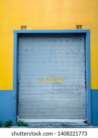 Urban yellow and blue wall with silver metal roller door with stencil NO PARKING on street with weeds