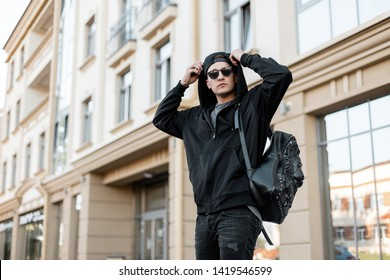Urban young hipster man in a trendy hooded sweatshirt with sunglasses in a black cap with a stylish backpack in jeans travels around the city on a bright summer day. Modern guy on the street.
