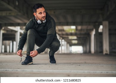 Urban young jogger tying his running shoes