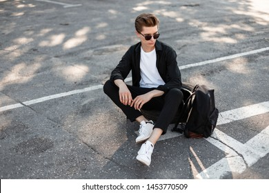 Urban young man hipster with hairstyle in sunglasses in elegant fashionable clothes in white sneakers rest in the city on a sunny day. Nice guy relaxes in the sun sitting on the asphalt. Street style.