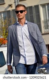 Urban young model man walking on street wearing sunglasses.