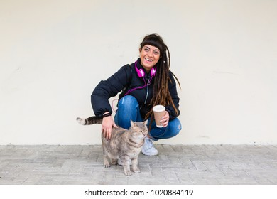 Urban Young Woman with Dreadlocks Caressing a Stray Cat