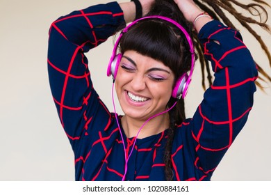 Urban Young Woman with Dreadlocks Listen to Music with Pink Headphones