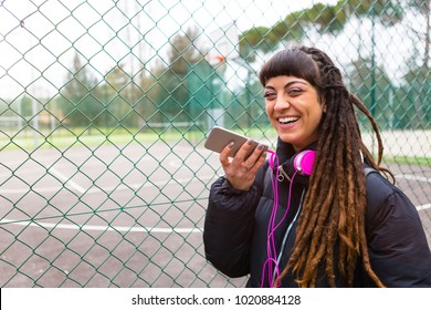 Urban Young Woman with Dreadlocks Sendind Voice Message with Mobile Phone