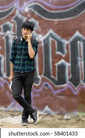 Urban youth talking on mobile phone in front of wall with graffiti