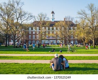 URBANA, ILLINOIS - APRIL 17, 2016:  Students and couples mingle on Quad lawn of University of Illinois college campus in Urbana Champaign