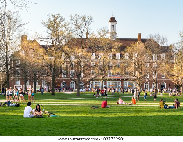 URBANA, ILLINOIS - APRIL 17, 2016:  Students walk and sit outside on Quad lawn of University of Illinois college campus in Urbana Champaign