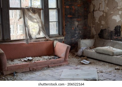 Urbex - Interior of abandoned house with broken sofas and asbestos tiles, in light HDR processing