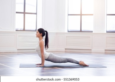 Urdhva mukha svanasana. Beautiful yoga woman practice in a training hall background with windows. Yoga or pilates concept.