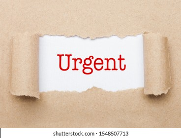 Urgent concept text appearing behind torn brown paper envelope