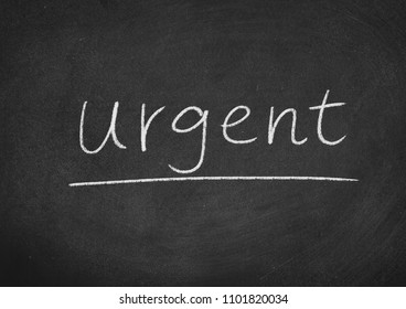 urgent concept word on a blackboard background