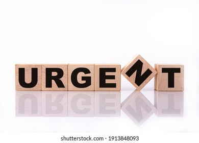 URGENT word, text, written on wooden cubes, building blocks, over white background with reflection.
