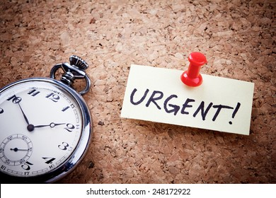 """Urgent!"" written on a post note and hanged on the cork-board with an old pocket watch."