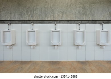 urinals in an building for men only, white urinals in men's bathroom, white ceramic urinals for men in toilet room