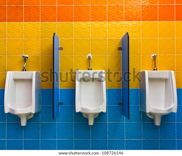 Urinals on colorful wall in public toilet