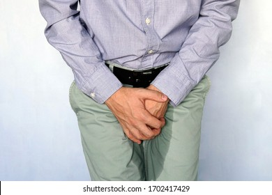 Urinary incontinence concept. Wet person. Blue background. adult man holds hands the groin area and trousers wet from urine. Health problem. Medical concept.