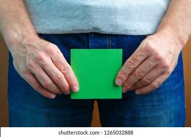 Urinary or prostate problems concept. Man holds sticker note near crotch. Copy spase