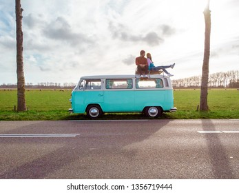 Urk Netherlands April 2019, couple having a picnic at countryside with old classic vw van, Classic Minty Green and white VW Camper Van parked  at countryside