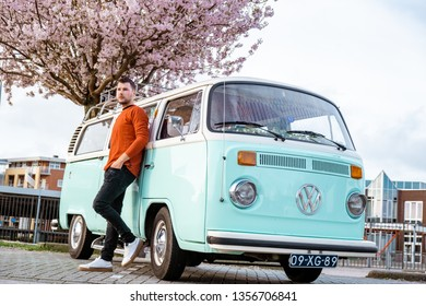 Urk Netherlands April 2019, men posing by classic Volkswagen van with blooming blossom tree
