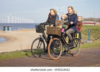Urk, The Netherlands - February 19 2021: Women with little kids at bycycle near Dutch coast of Urk, in the background a view at a big wind turbine farm
