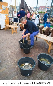 URK, NETHERLANDS - MAY 19, 2018: Unknown man cleaning eel on the annual Urker days. Urk is on of the best-known fishing villages in the country with the largest fishing fleet.