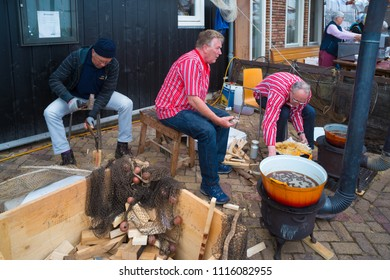 URK, NETHERLANDS - MAY 19, 2018: Unknown people frying fish in traditional costumes