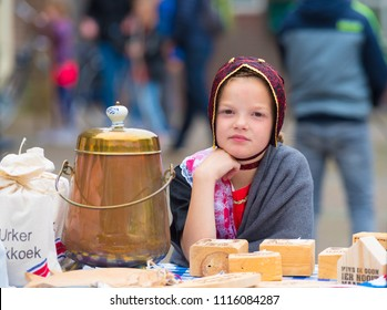 URK, NETHERLANDS - MAY 19, 2018: Unknown girl in traditional costume selling food on the Urkerdays. Urk is on of the best-known fishing villages in the country with the largest fishing fleet.