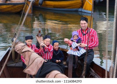 URK, NETHERLANDS - MAY 19, 2018: Unknown man and children in traditional costumes on the Urkerdays. Urk is on of the best-known fishing villages in the country with the largest fishing fleet.