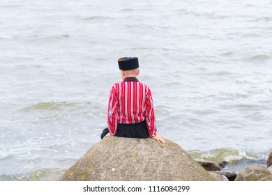 URK, NETHERLANDS - MAY 19, 2018: Unknown boy at the sea in traditional costume on the Urkerdays. Urk is on of the best-known fishing villages in the country with the largest fishing fleet.