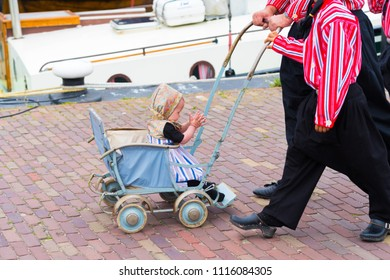 URK, NETHERLANDS - MAY 19, 2018: Unknown baby in a vintage stroller in traditional costume on the Urkerdays. Urk is on of the best-known fishing villages in the country with the largest fishing fleet.