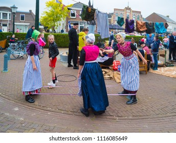 URK, NETHERLANDS - MAY 19, 2018: Unknown girls in traditional costumes playing an old-fashioned string game on the Urkerdays. Urk is on of the best-known fishing villages in the country