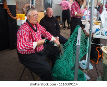 URK, NETHERLANDS - MAY 19, 2018: Unknown man in traditional clothes making fishing nets on the Urkerdays. Urk is on of the best-known fishing villages in the country with the largest fishing fleet.