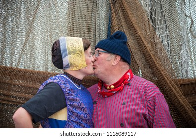 URK, NETHERLANDS - MAY 19, 2018: Unknown couple in traditional costumes kissing each other on the Urkerdays. Urk is on of the best-known fishing villages in the country with the largest fishing fleet.