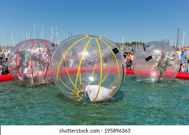 URK, THE NETHERLANDS - MAY 31: Children have fun inside big plastic balloons on the water during a fishing fare on May 31, 2014 at the harbor of Urk, the Netherlands
