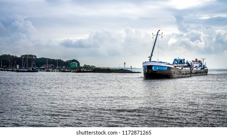 Urk, The Netherlands - Oct. 17, 2014: Large Cutter Suction Dredger vessel entering the harbor of the historic fishing village of Urk in the Netherlands