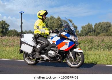 Urk, The Netherlands- September 08, 2012: Motorcycle policeman riding in rural landscape near Urk, The Netherlands
