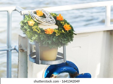 Urn with funeral flowers arrangement as burial at sea concept