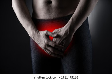 Urological genital infections concept, pain in prostate, man suffering from prostatitis or from a venereal disease on black background