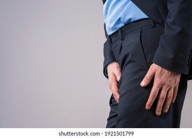 Urological genital infections concept, pain in prostate, office worker suffering from prostatitis or from a venereal disease on gray background