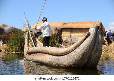Uros man rowing a reed boat next to his floating island on Lake Titicaca