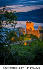 Urquhart Castle at twilight. The castle sits beside Loch Ness, near Inverness and Drumnadrochit, in the Highlands of Scotland. Only the bright part of the castle is in focus; the rest is blur.