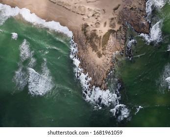 Uruguay, Punta del diablo. Vista aérea de la playa y el mar. Las olas rompen contra la arena y rocas, el agua es verde y oscura.  Uruguay tiene estas playas salvajes y solitarias.