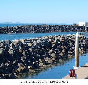 Urungan Marina. Rock break or training walls at the marina entrance. Waterfront walkway in tropical water with blue sky backdrop. Safe haven for cruising vessels. Urungan, Queensland, Austr