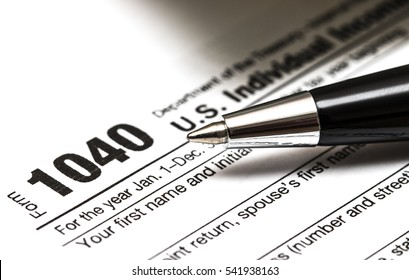 US 1040 tax form with pen, and coins