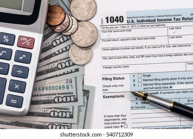 U.S. 1040 tax return form with dollar, pen and calculator.