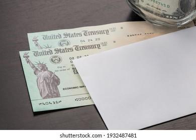US 1200, 600, 1400 dollar economic stimulus checks with dollar bills in the background