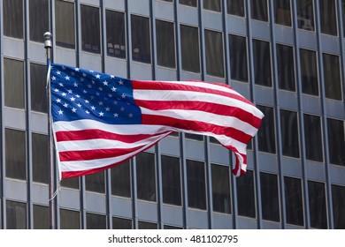 US american symbol flag over blue modern city buildings