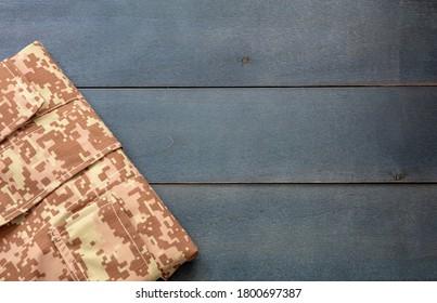 US army acu digital desert uniform shirt on blue wooden background. Military camouflage digital desert pattern folded shirt detail, copy space, template