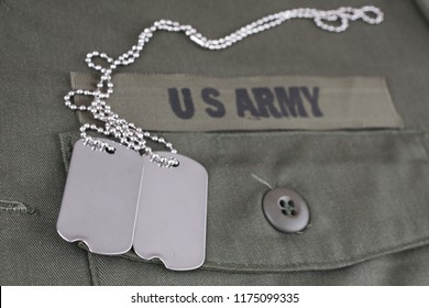 U.S. Army Branch Tape with dog tags on olive green uniform background