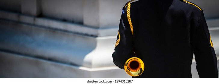 A US Army bugler stands at attention and ready to sound taps at a cemetery in Virginia.